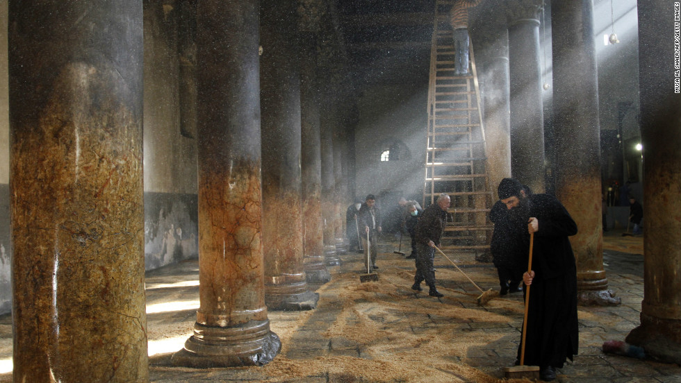 Orthodox clergy cleaning the Church of Nativity. Responsibilities for cleaning the church are split between the three denominations that administer the church, who have been known to erupt in scuffles.