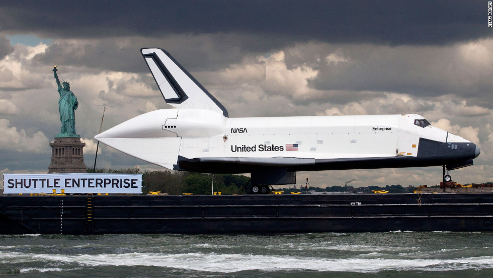 A barge carries the Space Shuttle Enterprise past the Statue of Liberty in New York Harbor on Wednesday, June 6. The shuttle is on its way to the USS Intrepid Museum, where it will be on display aboard the former aircraft carrier.