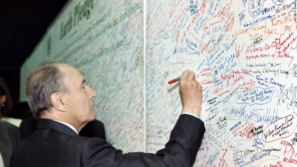 "French President François Mitterrand signs an ""Earth pledge,"" during the 1992 Earth summit."