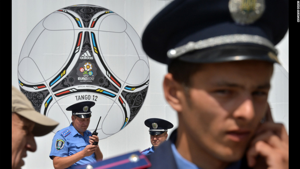 Police officers stand in front of a poster showing a giant ball.