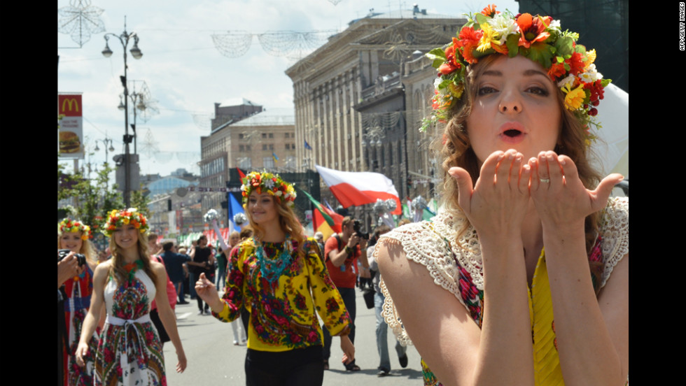 A young woman blows a kiss as she takes part in a parade before the opening match.