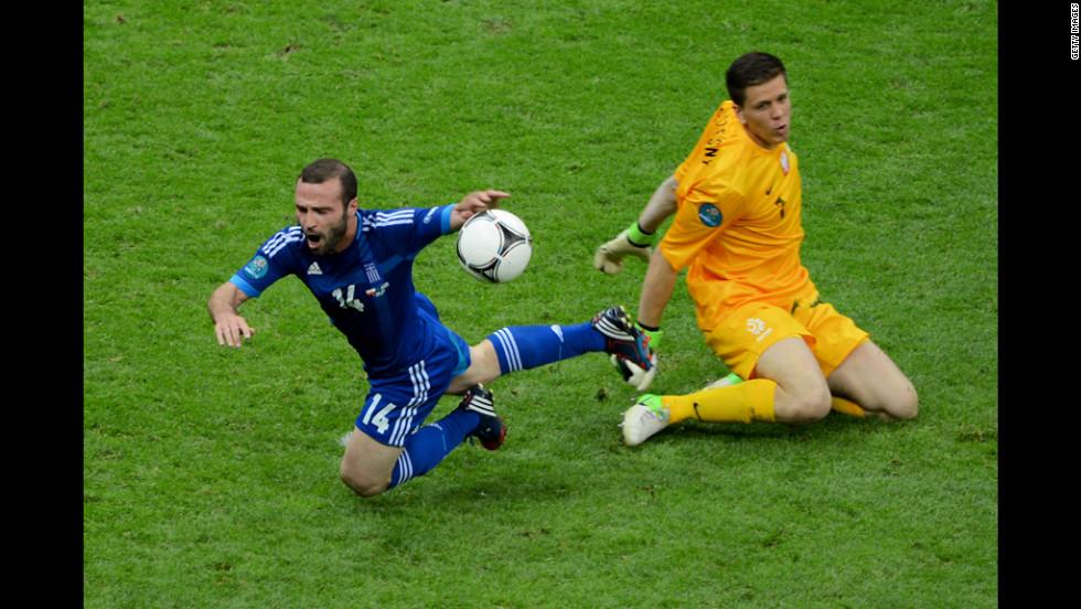 Wojciech Szczesny of Poland fouls Dimitris Salpigidis of Greece for a penalty.