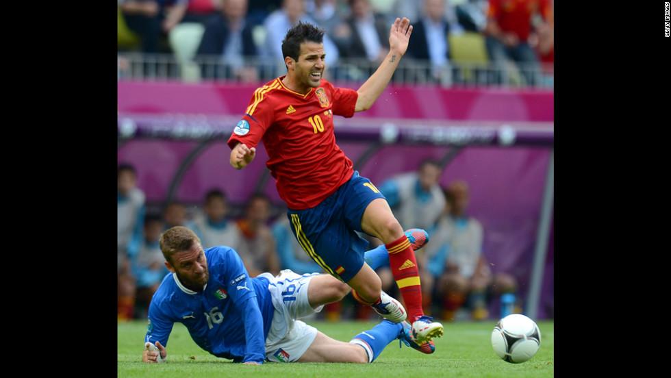 Daniele De Rossi of Italy tackles Cesc Fabregas of Spain.