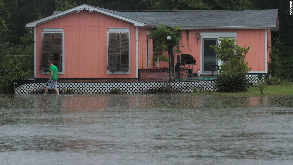 Josh Spinner checks his home surrounded by floodwaters Sunday in Perdido, Florida.