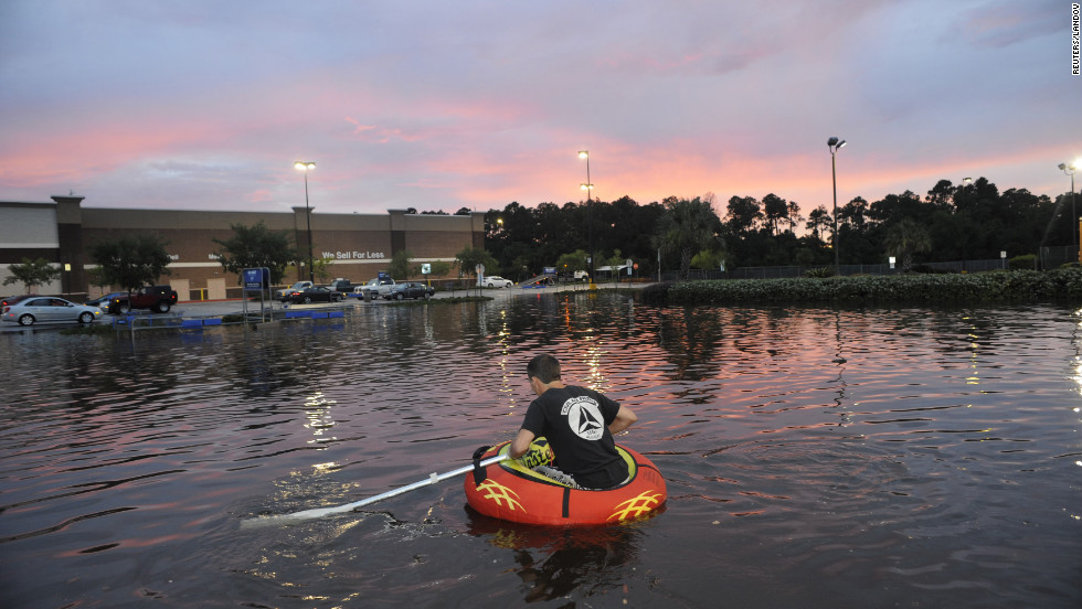 Robby Mandel, 16, navigates a flooded parking lot in Pensacola, Florida, on Saturday, June 9, as torrential rains inundate the Florida Panhandle and coastal Alabama.