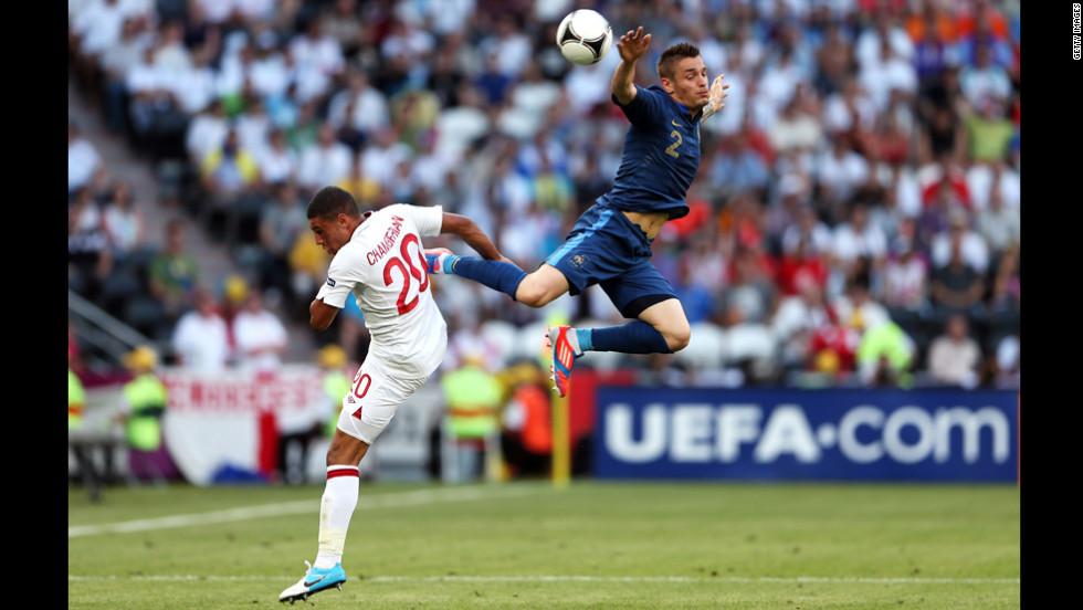 Mathieu Debuchy of France flies through the air as he battles England's Alex Oxlade-Chamberlain.