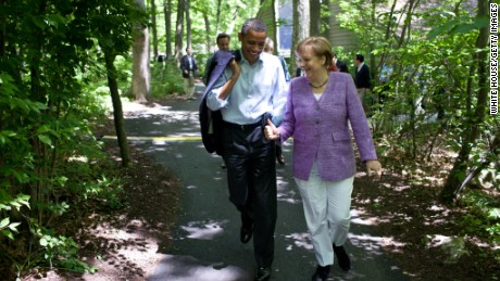 President Barack Obama talks with German Chancellor Angela Merkel as they walk through woodland at Camp David, Maryland, during the G8 Summit on May 19, 2012.