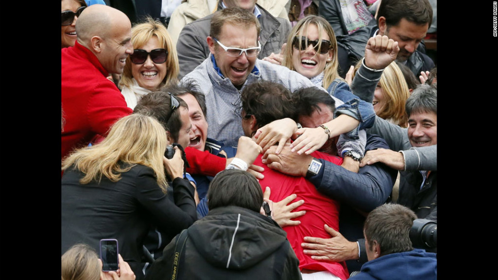 Nadal is embraced by friends and family in the stands after his victory.