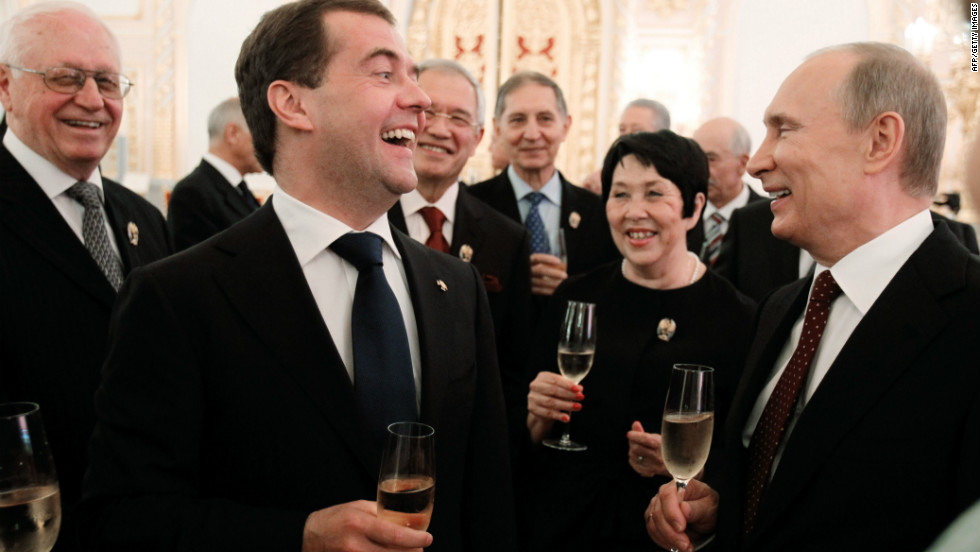 As protests took place nearby, Russia's President Vladimir Putin, right, and Prime Minister Dmitry Medvedev, second left, clink glasses in the Great Kremlin Palace in Moscow.
