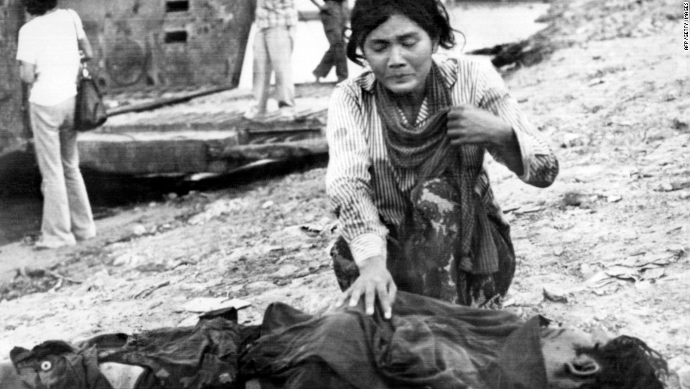 A woman cries next to a dead body on April 17, 1975 in Phnom Penh, after the Khmer Rouge entered the Cambodian capital to establish the government of Democratic Kampuchea.
