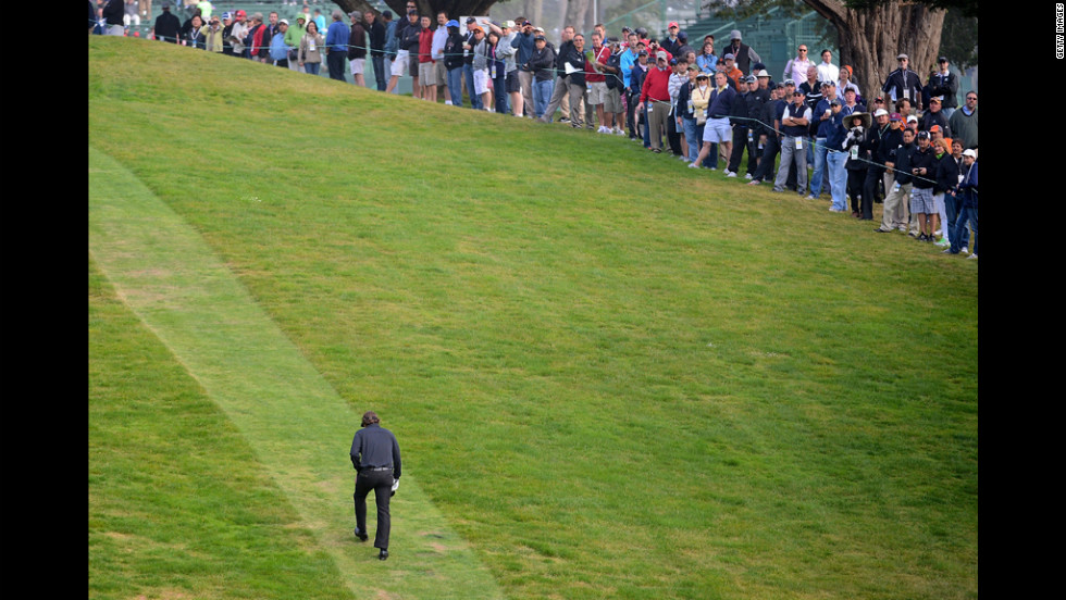 Spectators watch as Mickelson heads up the hill to the tee on the ninth hole.