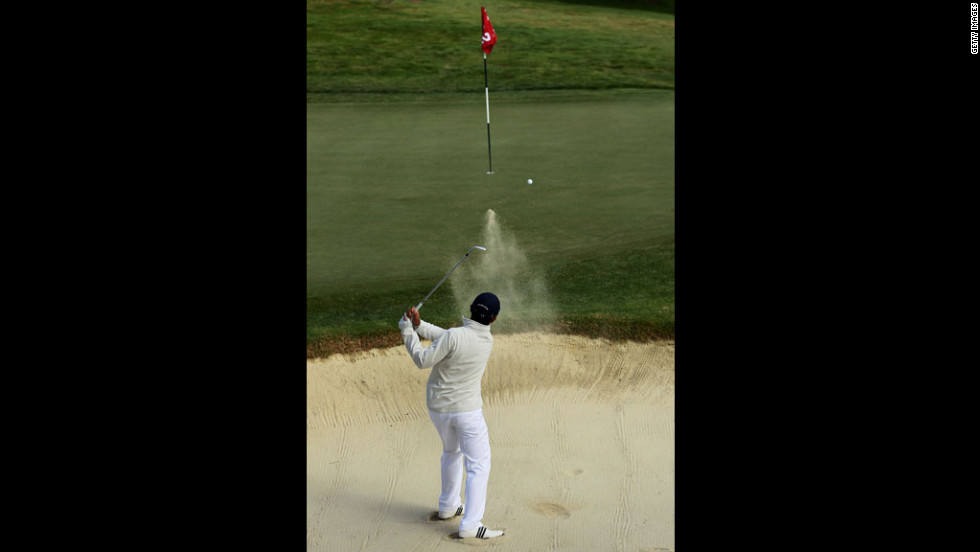 Andy Zhang, a 14-year-old originally from China, hits a bunker shot on the second hole.