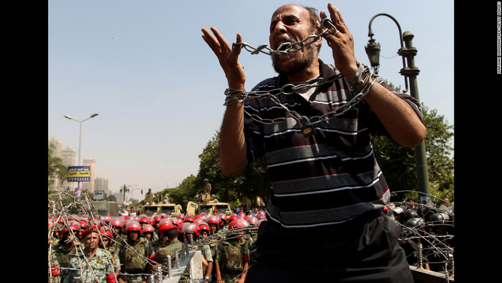 An Egyptian protester raises his hands symbolically wrapped in chains Thursday during a demonstration outside the Supreme Constitutional Court in Cairo.