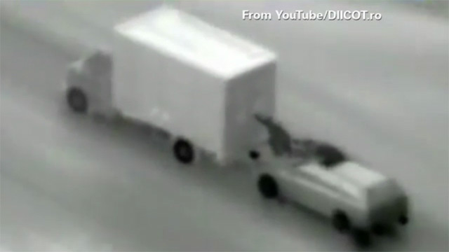 An alleged criminal gang in Romania is caught on aerial surveillance video trying to pull off a heist on a moving truck.