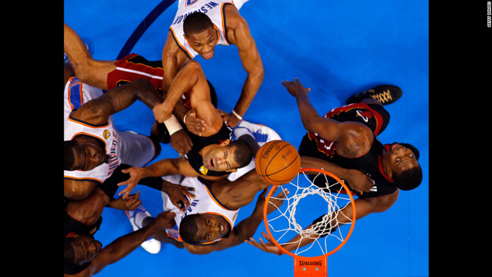 The Heat's Shane Battier and the Thunder's Serge Ibaka look up for a rebound.
