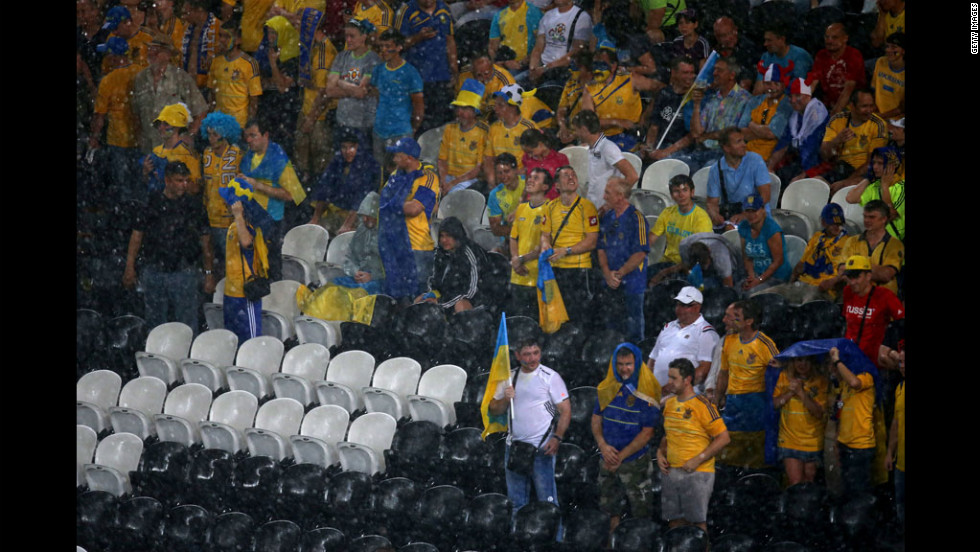 Fans endure the rains during the match between Ukraine and France.