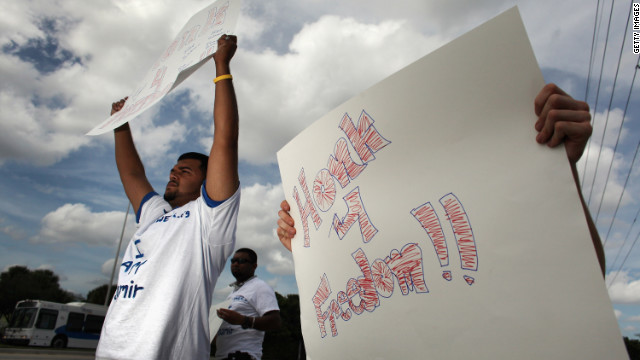 Safa Rafique holds a sign reading ' Honk 4 Freedom'' as he and others protest in front of the Broward Transitional Center on October 25, 2011 in Pompano Beach, Florida. The group was protesting the possible deportation of Shamir Ali, a 25-year-old born in Bangladesh, who they say would be a candidate for the DREAM Act if it was made into a federal law.