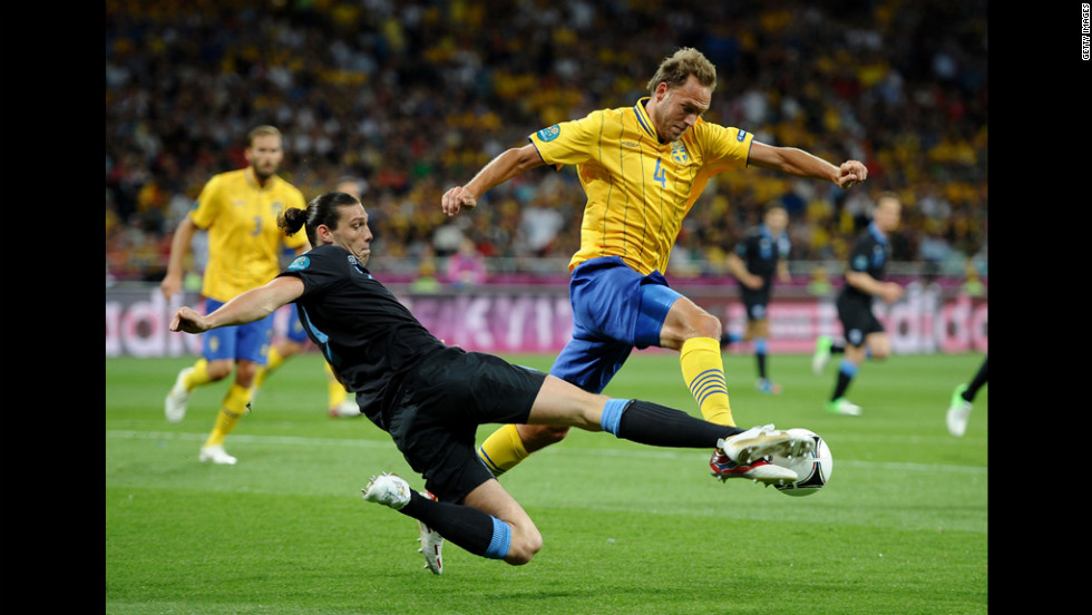 Andreas Granqvist of Sweden is tackled by Andy Carroll of England during the Sweden-England matchup.