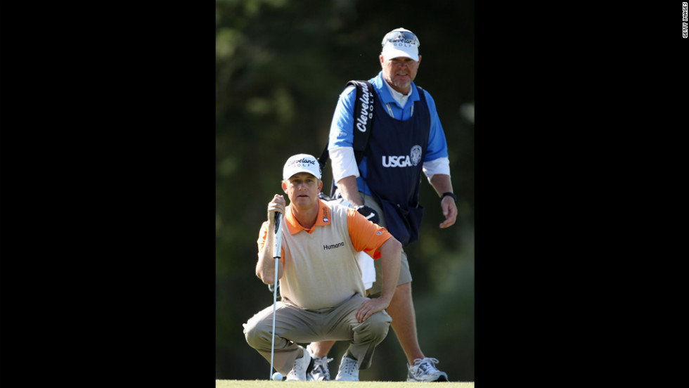 Caddie Scott Gneiser watches David Toms of the United States line up a shot during the second round.