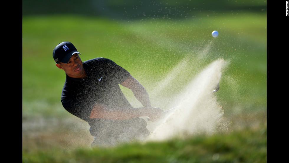 Tiger Woods plays a bunker shot on the 16th hole.