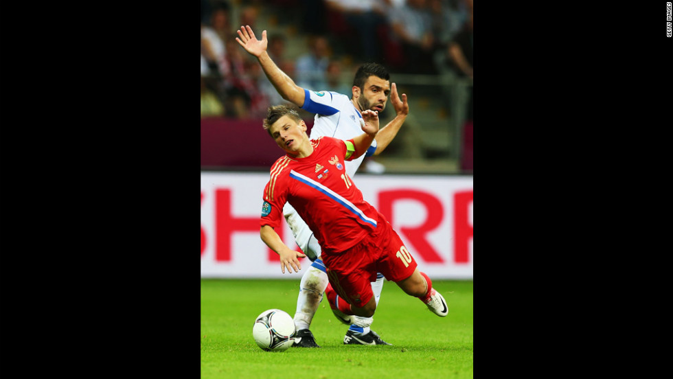 Andrey Arshavin of Russia falls under the challenge by Giorgos Tzavelas of Greece during the the match between Greece and Russia.