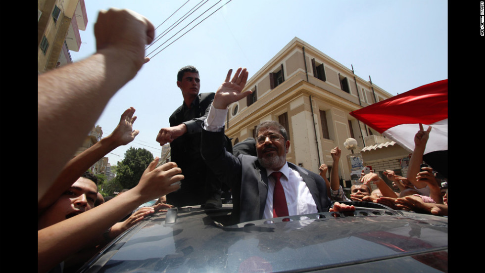 Egyptian Muslim Brotherhood candidate Mohammed Morsi, center, waves to his supporters as he arrives at a polling station to vote in the city of Zagazig.