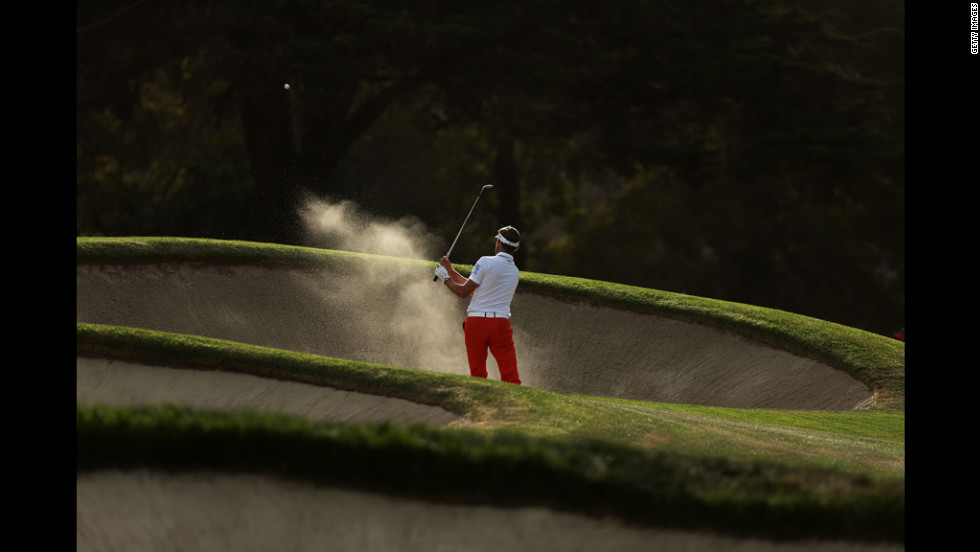Raphael Jacquelin of France hits a bunker shot on the 17th hole during the third round.