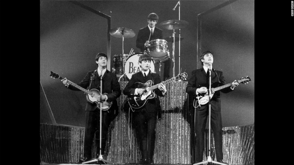 "The Beatles, whose arrival in the U.S. in 1964 set off ""Beatlemania,"" perform on stage at the London Palladium in 1963."