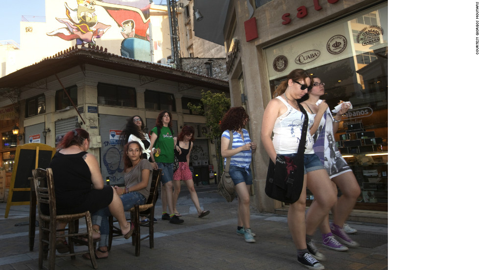 Young Greek people walk through Psiri, an area regarded as one of Athens most vibrant art and cultural centers. However, business has dropped by 60%, and crime has increased, local workers say.