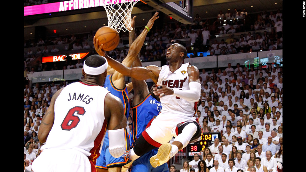 LeBron James watches as Dwyane Wade attempts a shot in the first half.