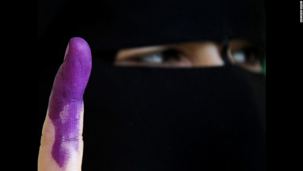 An Egyptian woman shows her ink-stained finger, marking that she voted in Cairo on Sunday.