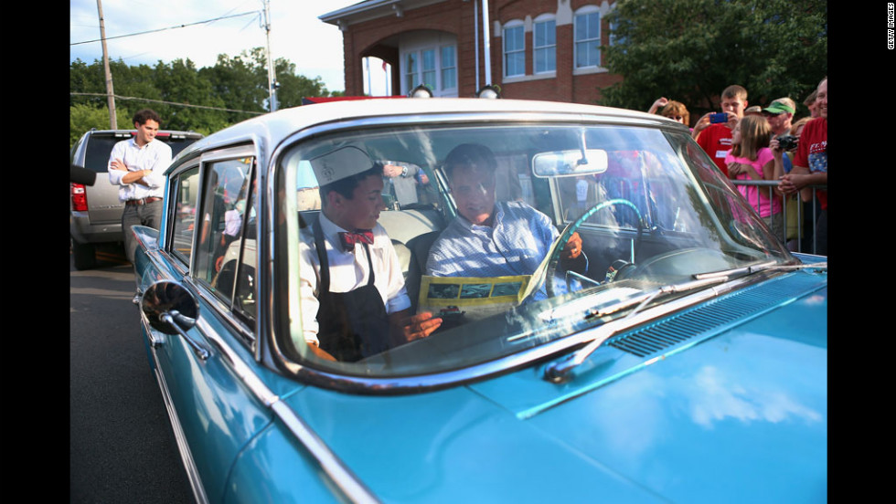 Republican presidential candidate Mitt Romney sits in a 1961 Rambler owned by Michael Scheib, left, during a campaign event Sunday at K's Hamburger in Troy, Ohio. Romney's father, George Romney, was the chairman and president of American Motors Corp., which made the Rambler.