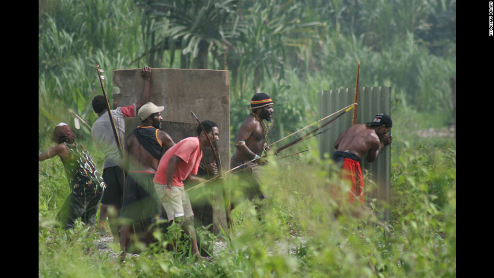 Papuan tribal warriors armed with bows and arrows and improvised shields move into position as clashes erupted anew Monday between two tribes in Kwamki Lama village in Indonesia's restive Papua province.