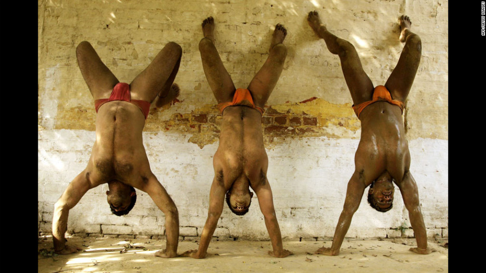Indian Kushti wrestlers perform preform handstands while warming up before a practice session in the mud on Monday at a Kushti training center, in the northern Indian city of Allahabad.