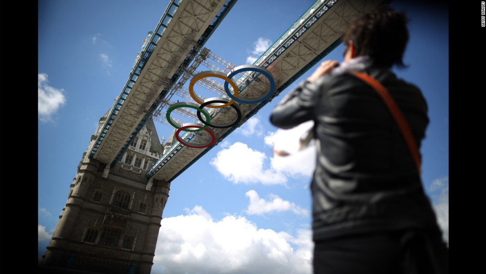 A woman takes a picture as giant Olympic rings are installed under the walkways of London's Tower Bridge on Monday.