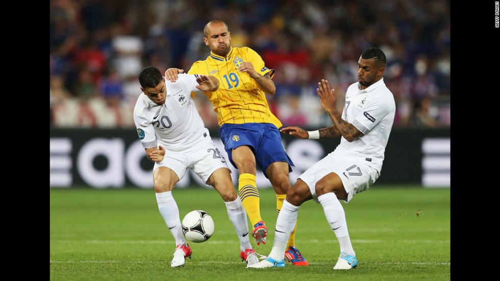 Emir Bajrami of Sweden gets tackled by France's Hatem Ben Arfa, left, and Yann M'Vila during a Group D match Tuesday in Kiev, Ukraine.