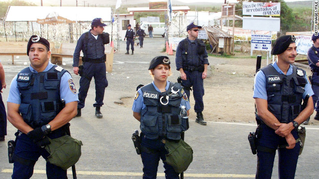 VIEQUES, PUERTO RICO: Puerto Rican police (front) and US Marshals (rear) stand in front of the main gate of the US Navy's Camp Garcia in Vieques, Puerto Rico 04 May, 2000. Marshals peacefully arrested about 60 people for blocking the gate to the base while prostesting against the Navy use of the site for a bombing range. The Puerto Rican police did not participate in the arrests. (ELECTRONIC IMAGE) AFP PHOTO/Robert SULLIVAN (Photo credit should read ROBERT SULLIVAN/AFP/Getty Images)