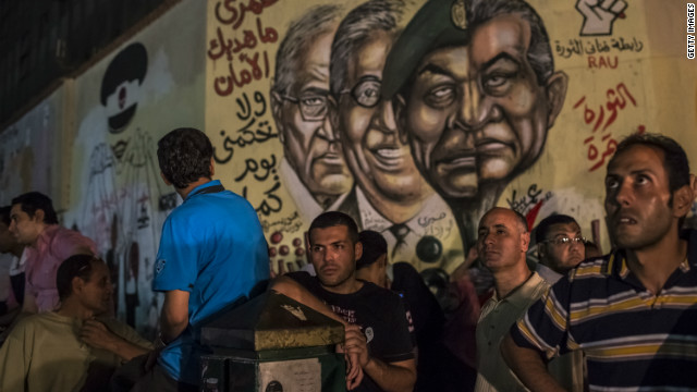 Egyptian men look on as graffiti showing faces of ousted Egyptian president Hosni Mubarak (R), head of the Egyptian ruling military council, Field Marshal Hussein Tantawi (2nd R), former Secretary General of the Arab League Amr Mussa (2nd L) and former prime minister and presidential candidate Ahmed Shafiq (L) is seen on a wall at Tahrir square on June 19, 2012 in Cairo, Egypt.