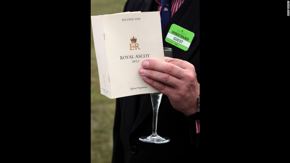 A visitor to Royal Ascot holds a race guide and a glass of Champagne.
