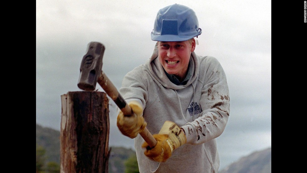Prince William hammers a log while helping construct walkways in a remote village in Chile during his Raleigh International expedition in 2000.