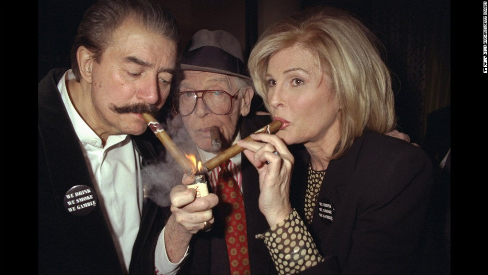 Milton Berle provides a light for his wife, Lorna, and Neiman in 1997.