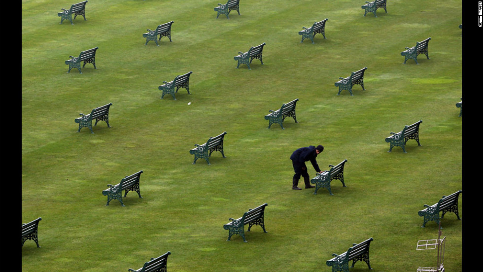 A worker checks benches in the grandstand.