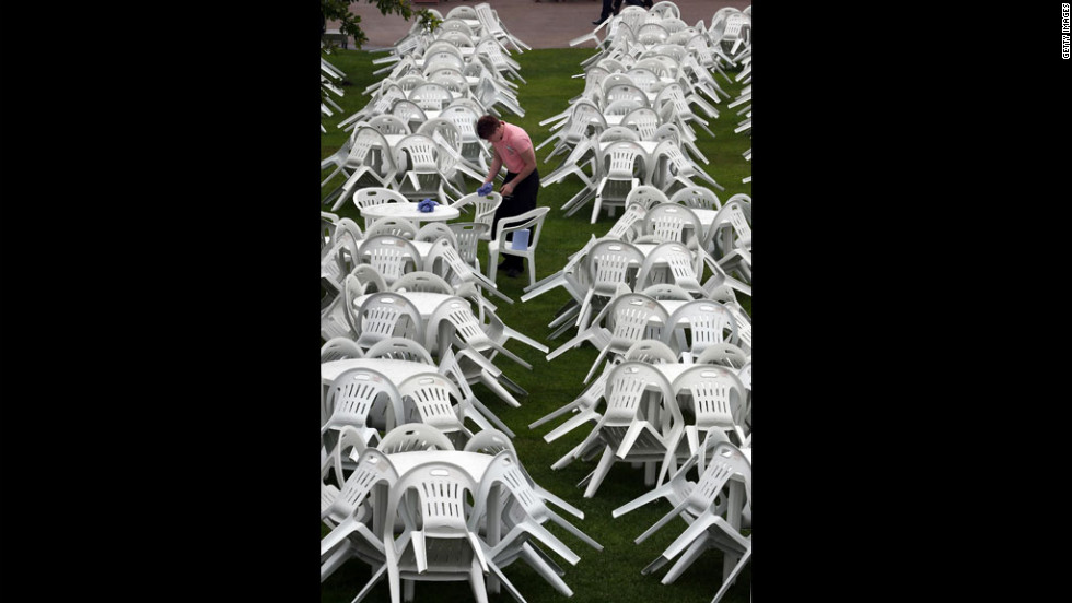 A worker attempts to dry tables and chairs at a Champagne bar on Ladies Day at Royal Ascot.