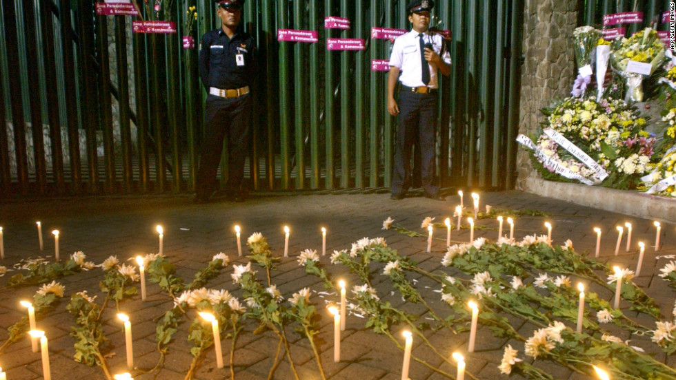 Two security guards stand in front of the Australian Embassy's front gate, where Indonesians placed candles and flowers to express their condolences for the victims of the Bali bombings.
