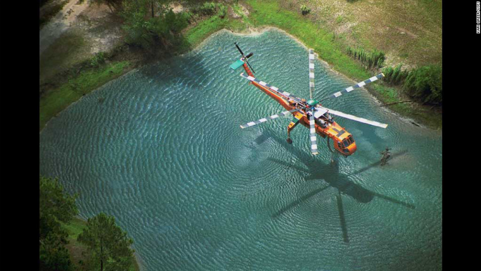 "This is Greer's award-winning image of an Erickson Air-Crane dipping into a pond to fill its tank on the Oakhead Complex Fire in Osceola National Forest, Florida. The image won first place in the ""aerial resources"" category of a Fire & Aviation Management photo contest in 2004."