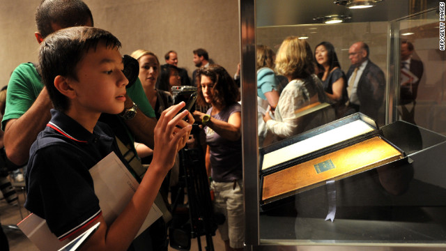 A boy takes a photograph of George Washington's personal copy of the U.S. Constitution and Bill of Rights.