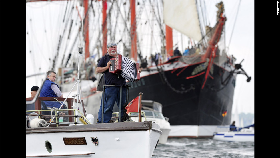 A man plays his accordion in front of the Russian tall ship Sedov at the Windjammer Parade.