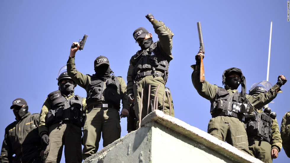 Armed mutinied policemen stand on the roof of a police headquarters in La Paz, on June 23, 2012 during a police strike demanding a salary increase.