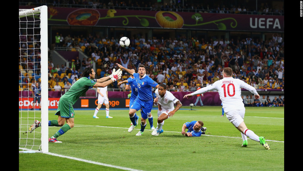 Gianluigi Buffon of Italy makes a save as Wayne Rooney of England runs in during the quarterfinal match.