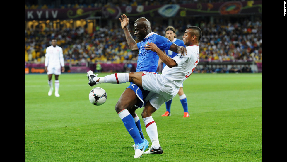 Mario Balotelli of Italy and Ashley Cole of England compete for control of the ball.